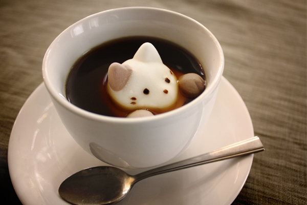 A marshmallow shaped like a kitty peeking out of a cup.